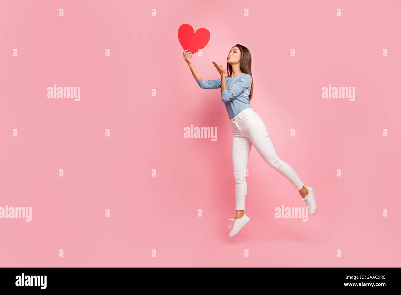 Full length body size side brown haired profile photo of cheerful positive cute pretty nice tender girl sending air kiss to heart held isolated pastel Stock Photo