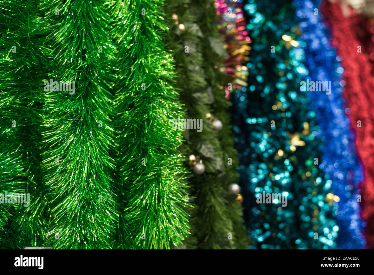 Multi Colored Garlands And Tinsel On A Store Counter Red Blue Green Christmas Tree Garland Hang On A Shelf In A Store Stock Photo Alamy