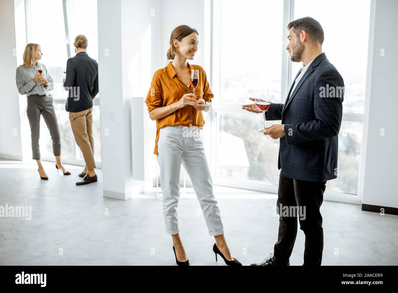 Young elegantly dressed people meeting in the white hallway or showroom, talking and drinking wine during some informal event Stock Photo