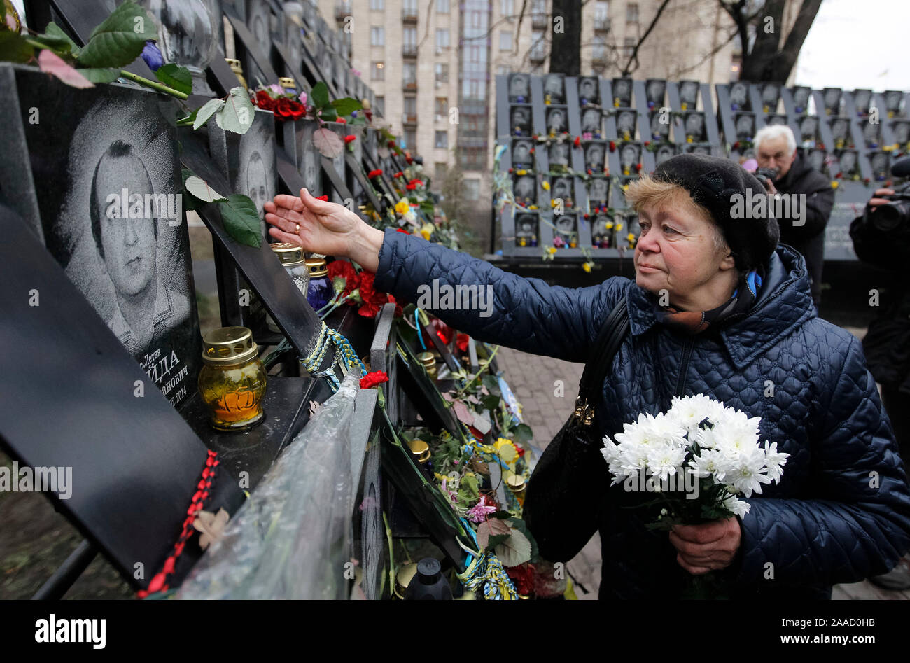 A woman holds flowers at the memorial of dead Maidan activists (Heroes of the Heavenly Hundred) during the anniversary in Kiev.Ukrainians mark the 6th anniversary of the beginning of the Revolution of Dignity or the Euromaidan Revolution in which more than hundred anti-government protesters died. Stock Photo