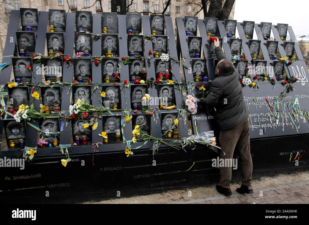 A man lays flowers to the memorial of dead Maidan activists (Heroes of the Heavenly Hundred) during the anniversary in Kiev.Ukrainians mark the 6th anniversary of the beginning of the Revolution of Dignity or the Euromaidan Revolution in which more than hundred anti-government protesters died. Stock Photo