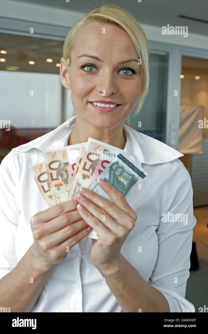 Junge blonde Frau zeigt verschiedene Euro Banknoten Stock Photo