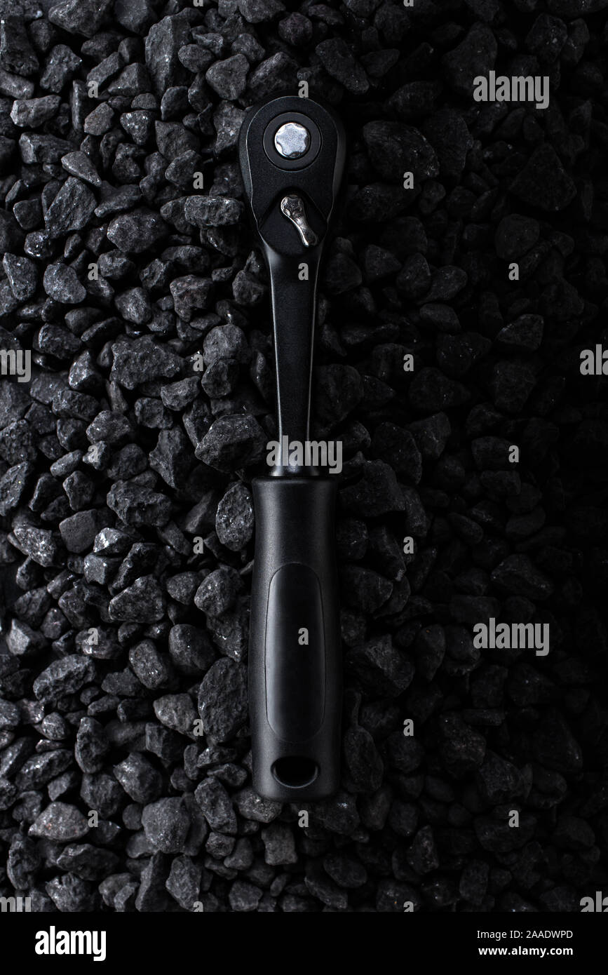 Professional reinforced black matt hex wrench placed on a stony background. View from the top. Stock Photo