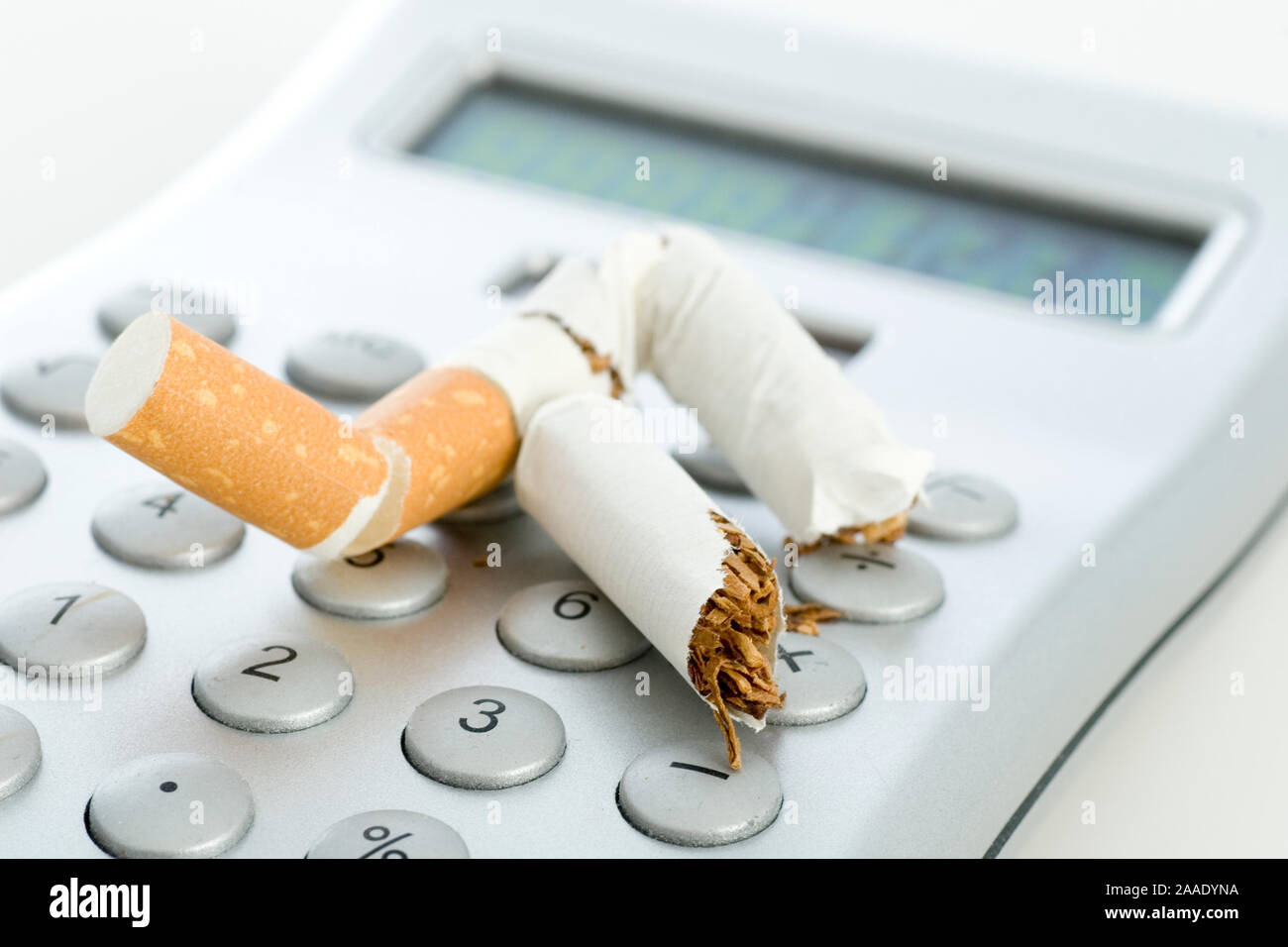 ausgedrückte Zigarette auf einem Taschenrechner Stock Photo