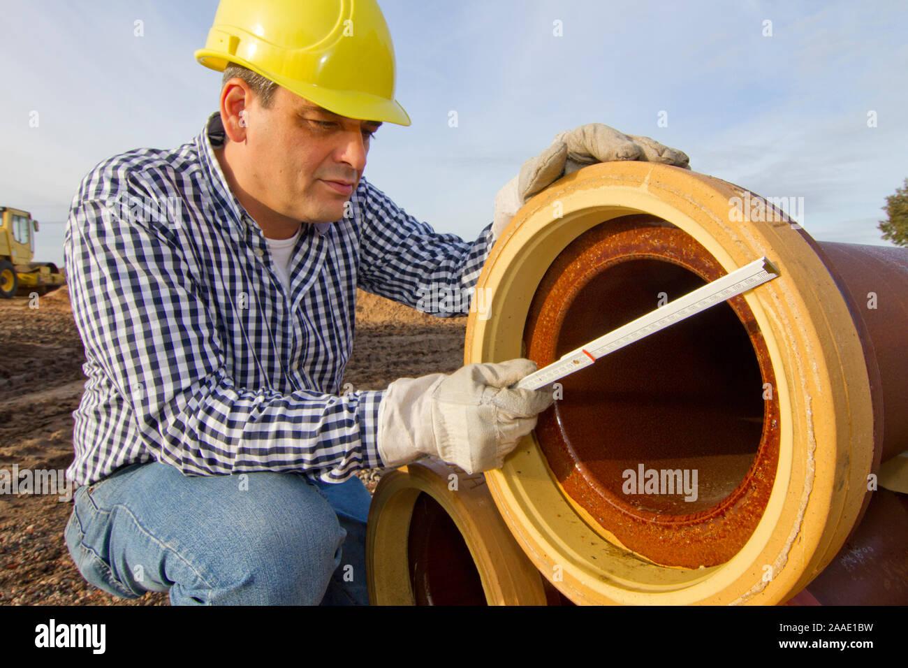 Bauarbeiter arbeitet mit Rohr Stock Photo