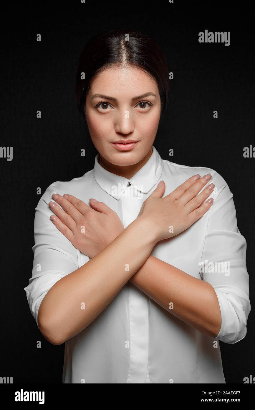 portrait of Asian brunette woman in white shirt with arms crossed on chest on black background Stock Photo