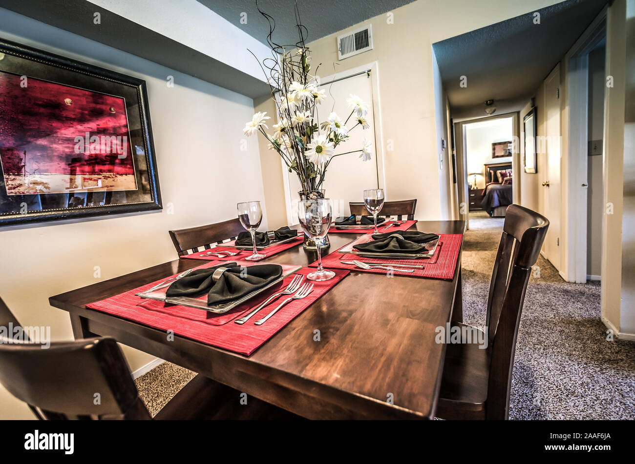 Red placemats complement the artwork in a dining room at Four Seasons apartments in Mobile, Alabama. Stock Photo