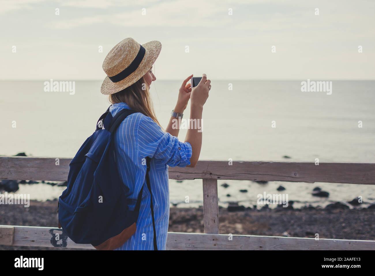 Woman traveler walking on Vlychada beach in Akrotiri on Santorini island, Greece. Tourist taking photo of sea Stock Photo