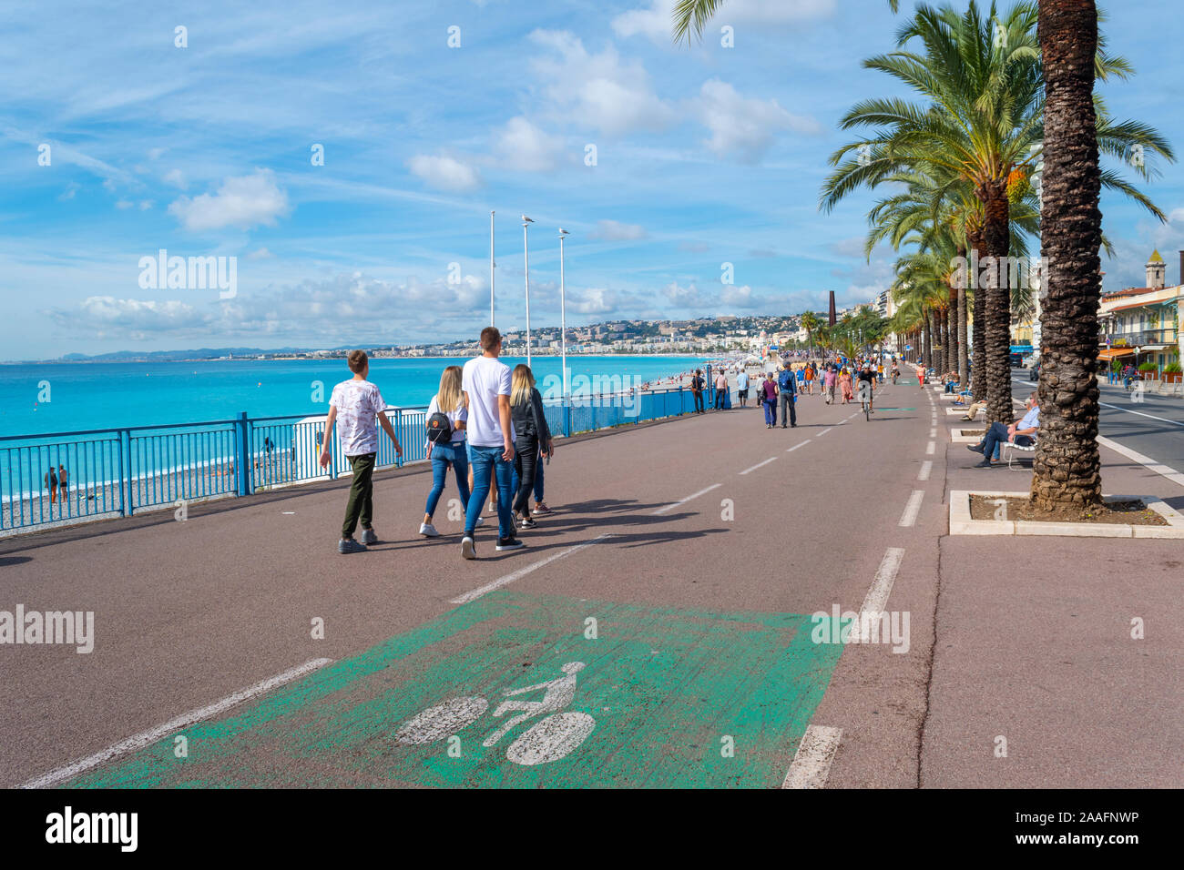 Pedestrians walk the Promenade Des Anglais on a sunny day on the French Riviera in Nice France. Stock Photo