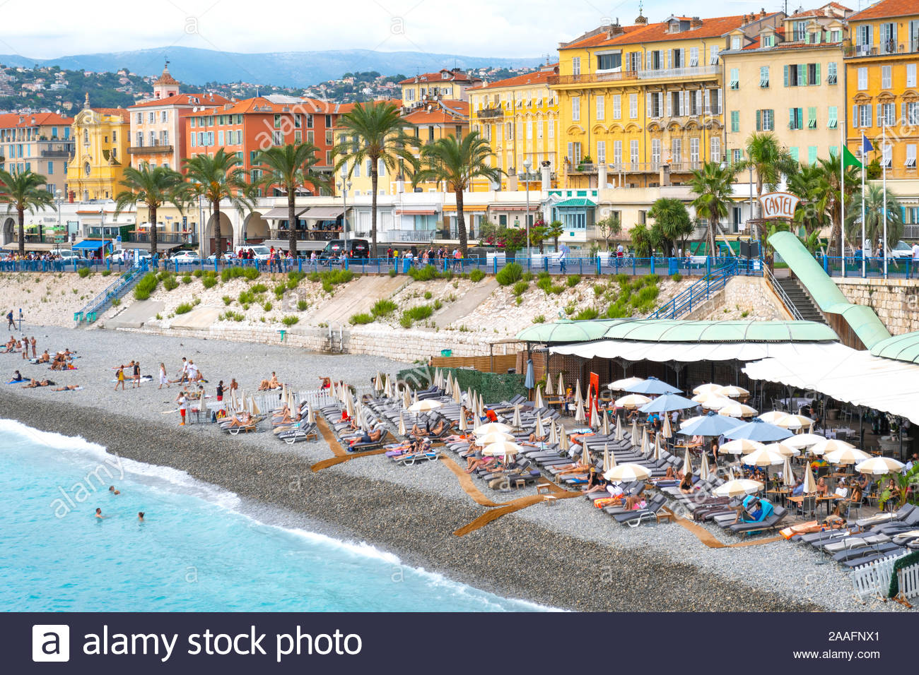 Tourists enjoy the Castel Plage private beach club and restaurant on the shores of the Bay of Angels on the Riviera in Nice, France Stock Photo