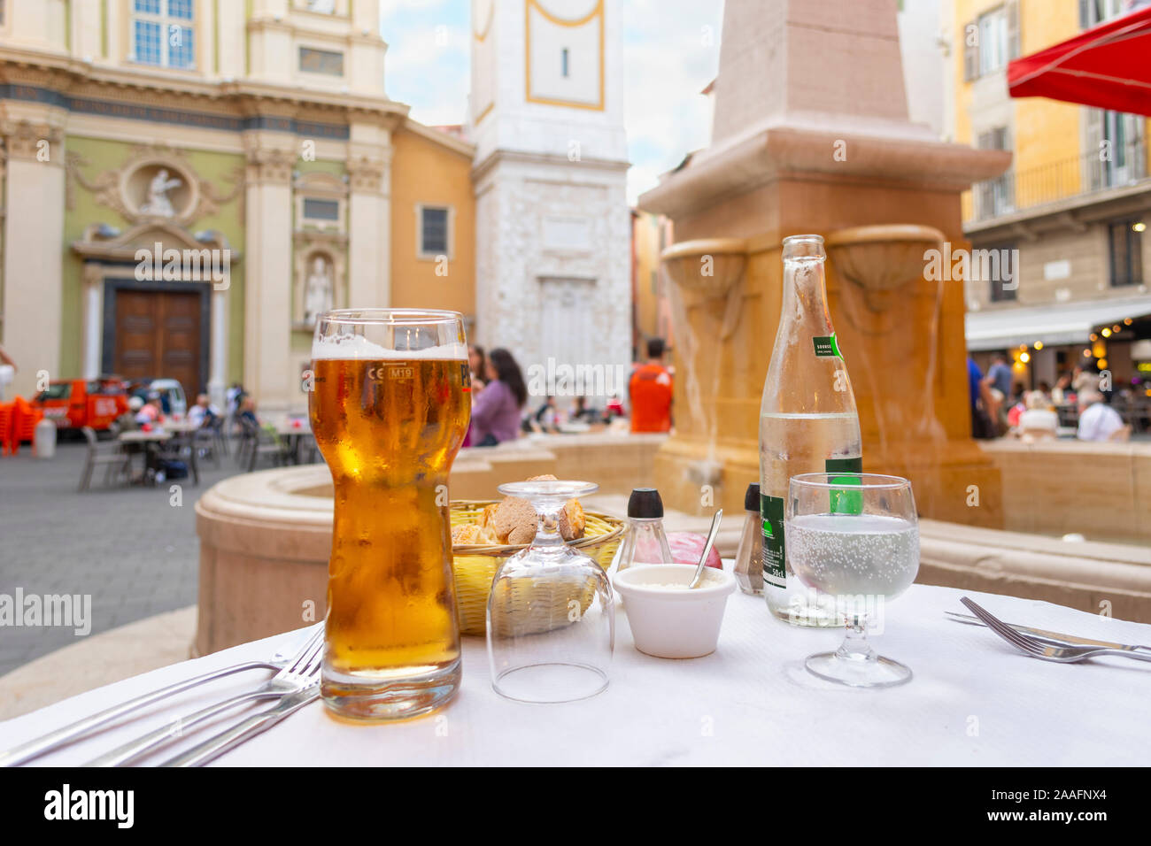 A basket of bread and rolls, a glass of beer and a bottle of water on a patio table in a piazza in front of a fountain in Nice France. Stock Photo