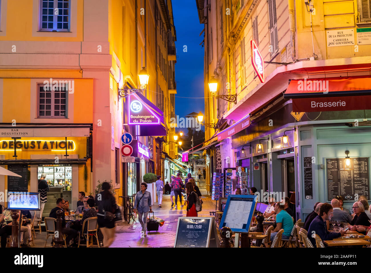 Colorful night view of tourists and local French enjoying sidewalk cafes in the old town Vieux Nice area of Nice, France. Stock Photo