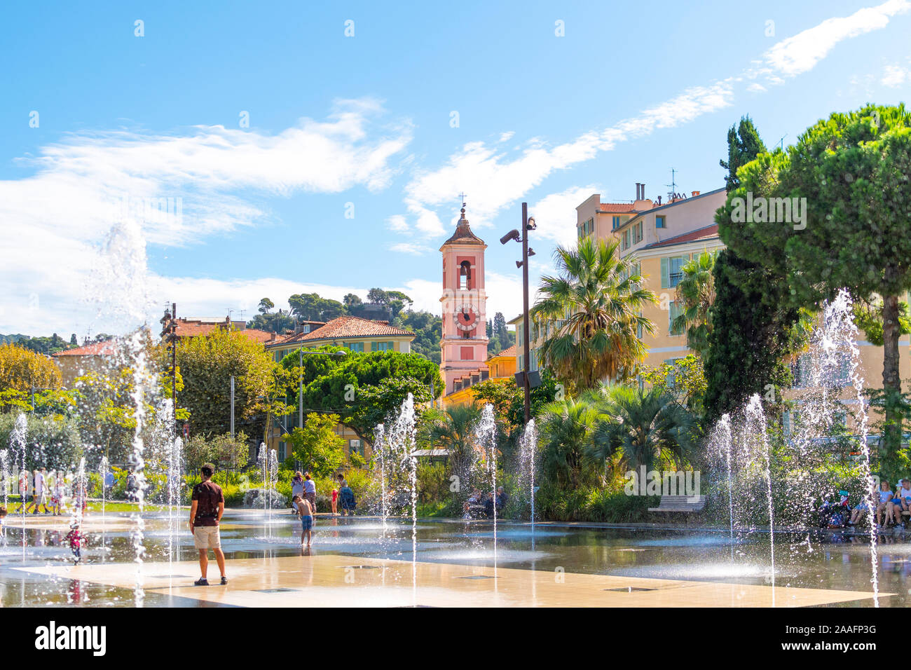 French adults and children play in the water fountain spray at the Paillon Promenade in the city of Nice, France on the French Riviera. Stock Photo