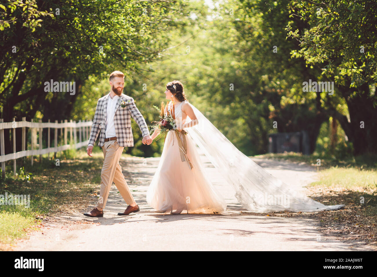 Lovely wedding couple wood forest. Bride and groom, follow me, married couple, woman in white wedding dress and veil. Rustic outdoors love story Stock Photo