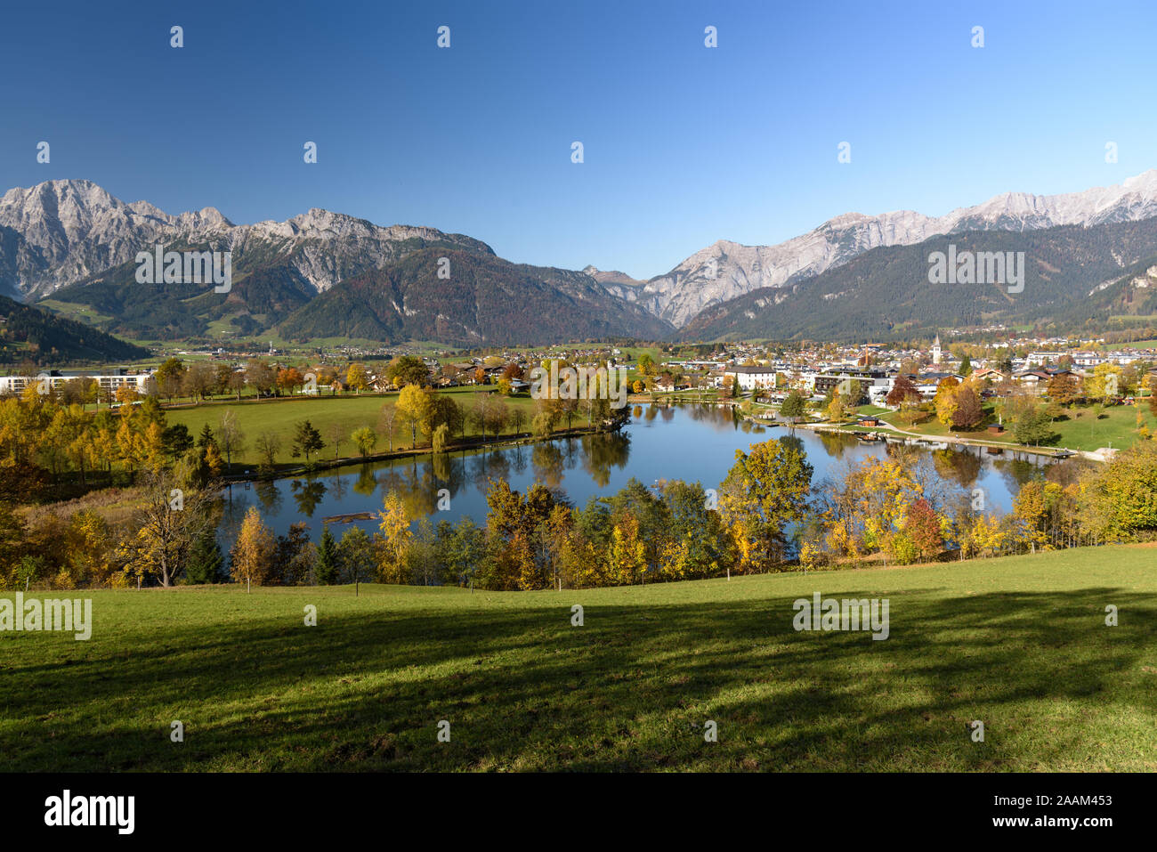 Panoramic view of Lake Ritzensee and Saalfelden on a sunny autumn day in with the mountains Steinernes Meer in the background. Saalfelden, Pinzgau, Sa Stock Photo