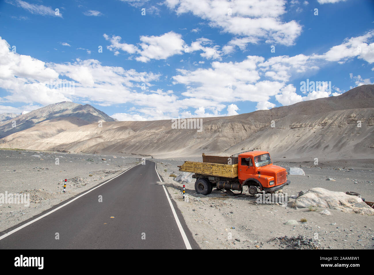 wreck of truck alongside empty road in Himalayas in Nubra valley in Ladakh, India Stock Photo
