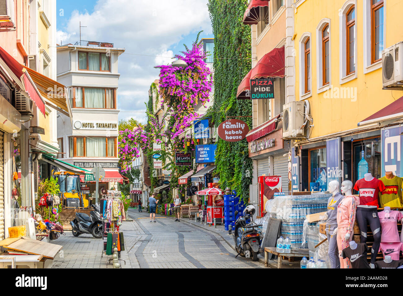 A colorful street of shops in the Sultanahmet District of Istanbul, Turkey, with lush plants and bougainvillea flowers adorning the walls. Stock Photo