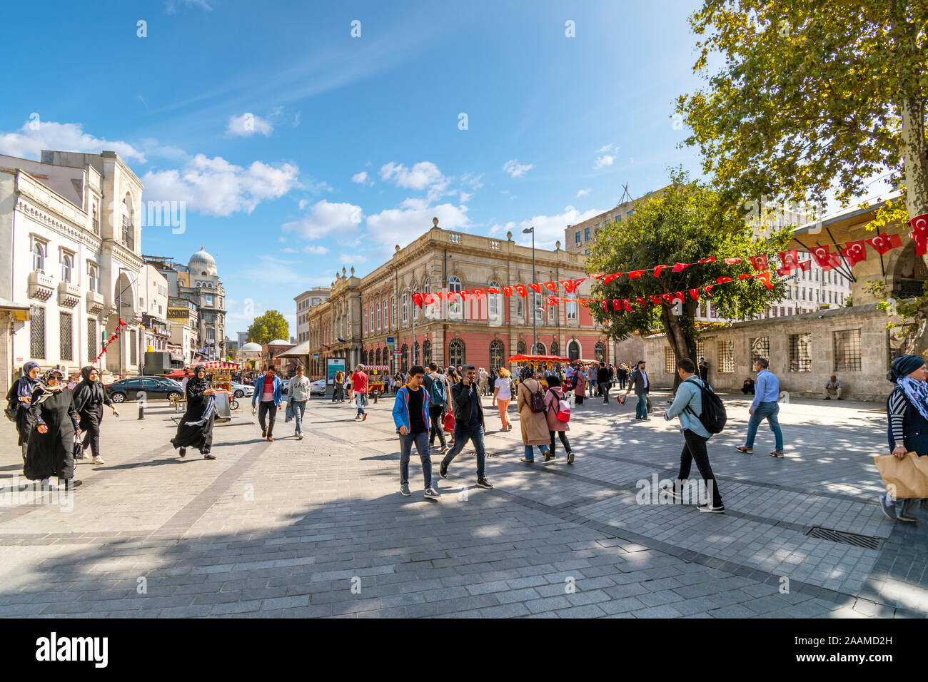 Tourists, and local Turks walk under Turkish Flags in Eminonu Square in Istanbul, Turkey. Stock Photo