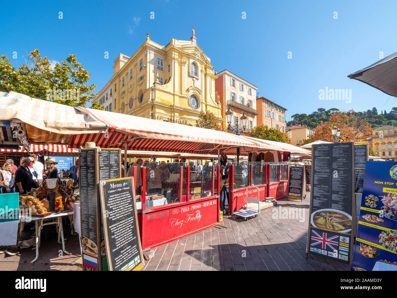 Tables with antiques and collectibles in the covered outdoor flea market alongside sidewalk cafes in the Cours Saleya market in Nice, France. Stock Photo