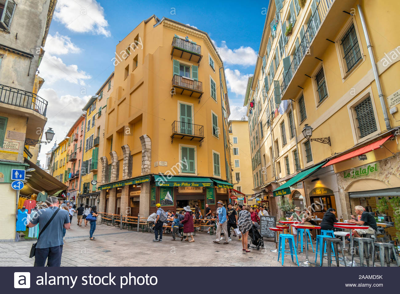 Tourists gather at one of the many sharp corners and turns in the twisty, winding Old Town of Vieux Nice, France, on the French Riviera Stock Photo