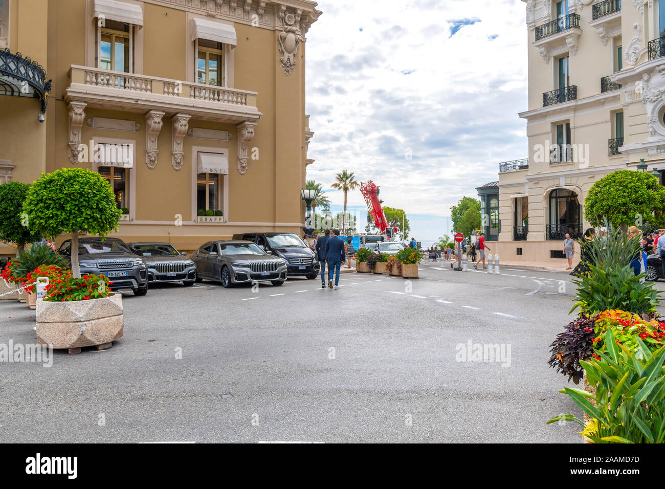 Two well dressed men leave the Monaco Casino parking lot on their way  to the harbor along the French Riviera. Stock Photo