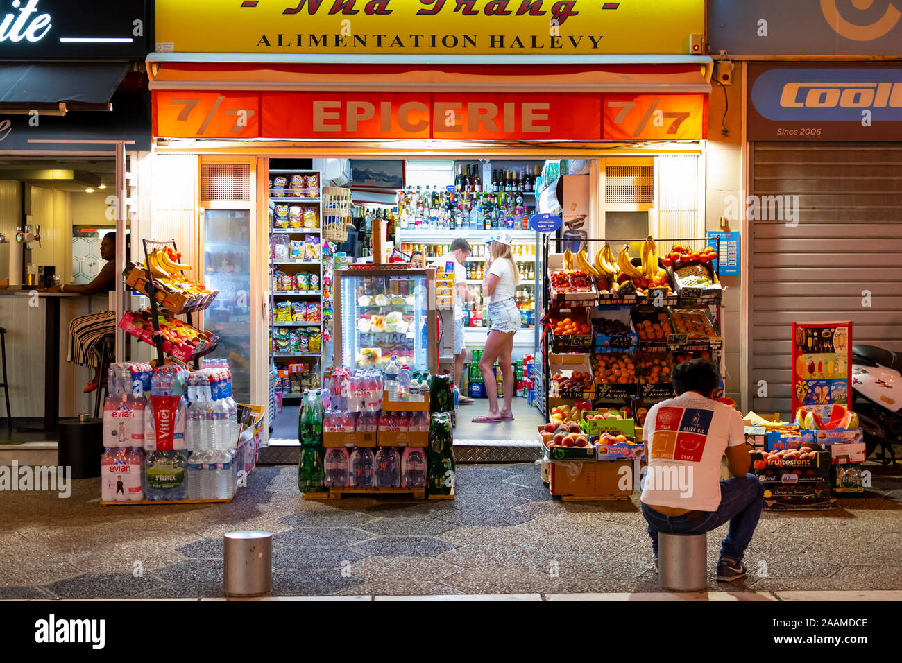 A young couple visits a colorful, brightly illuminated epicerie or grocery store late night in the tourist section of Nice, France Stock Photo
