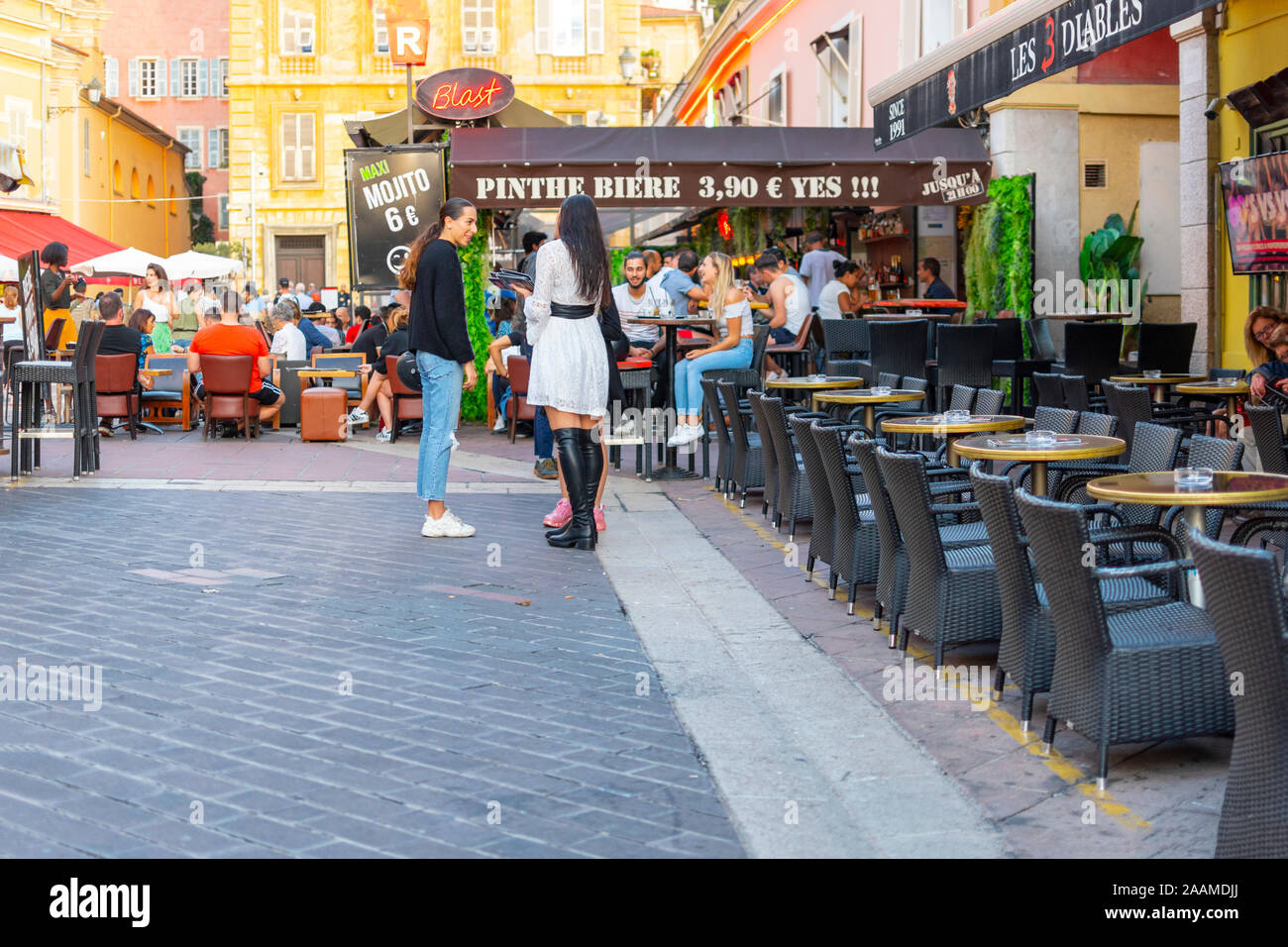 Young people congregate at the Cours Saleya Old Town area in Nice, France as diners enjoy an early dinner on the French Riviera. Stock Photo