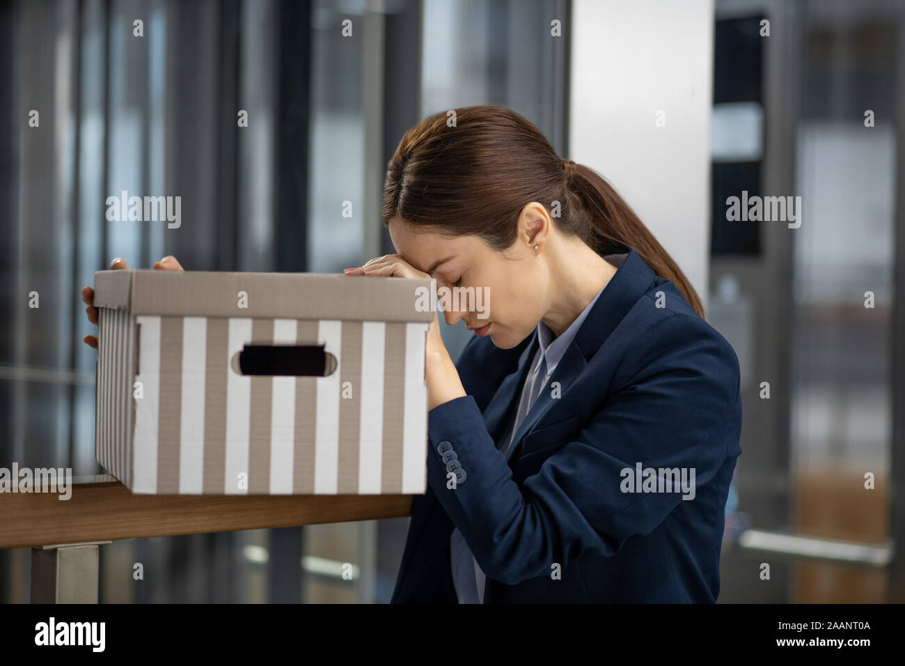 Dark-haired woman wearing dark jacket feeling awful after losing her job Stock Photo