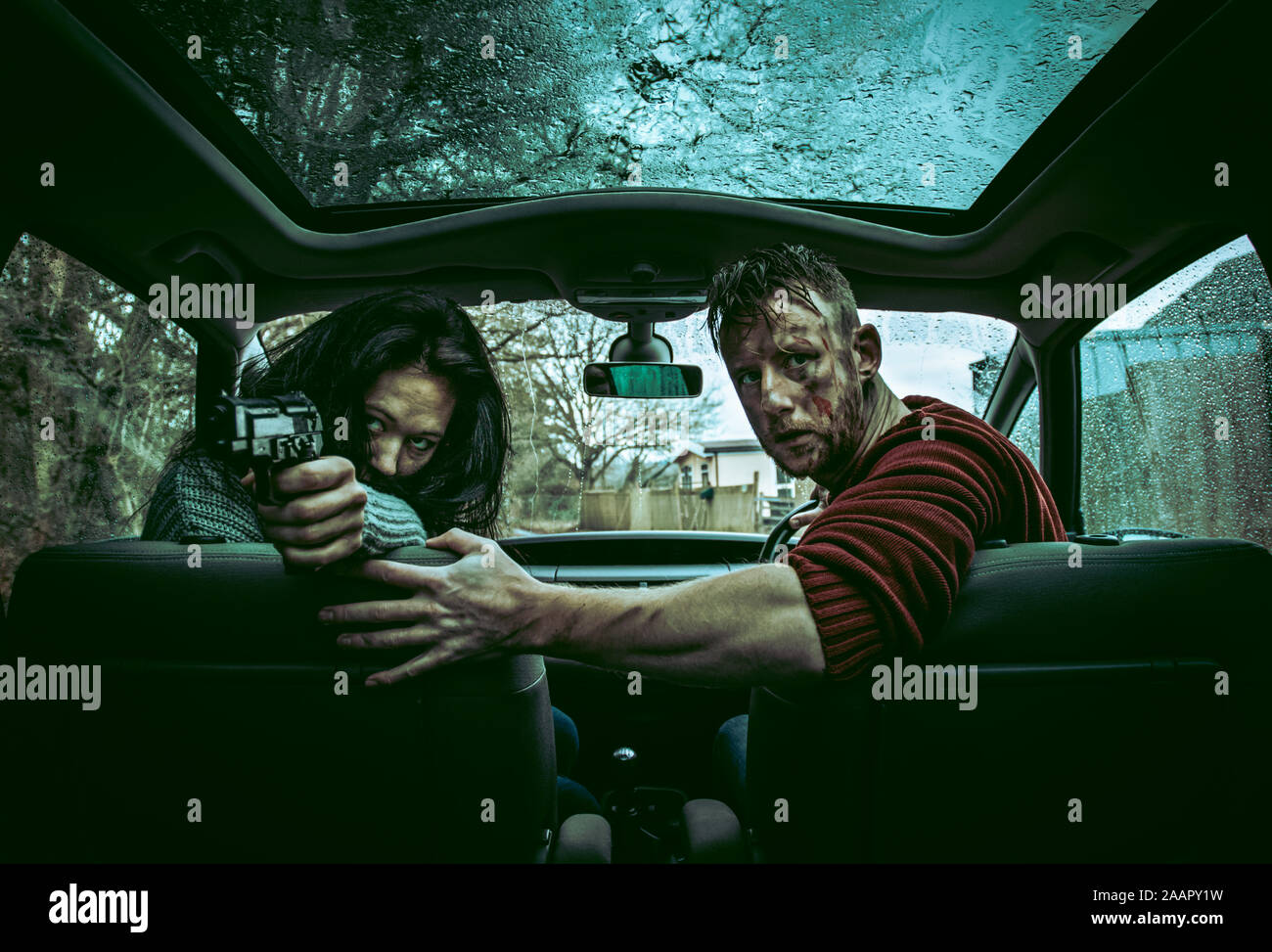 Two people, a male and female appear in danger or maybe they are the dangerous ones? they are sat in a car covers in dirt and weapon in hand Stock Photo