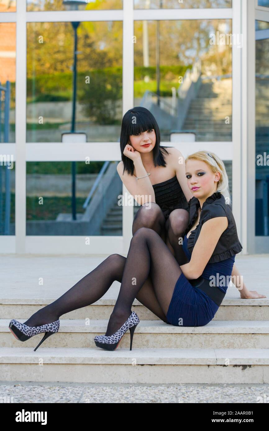 Popular schoolgirls posing in highheels before school slight smiling smile eyeshot heelsaddicted sitting on steps staircase town city urban frames Stock Photo