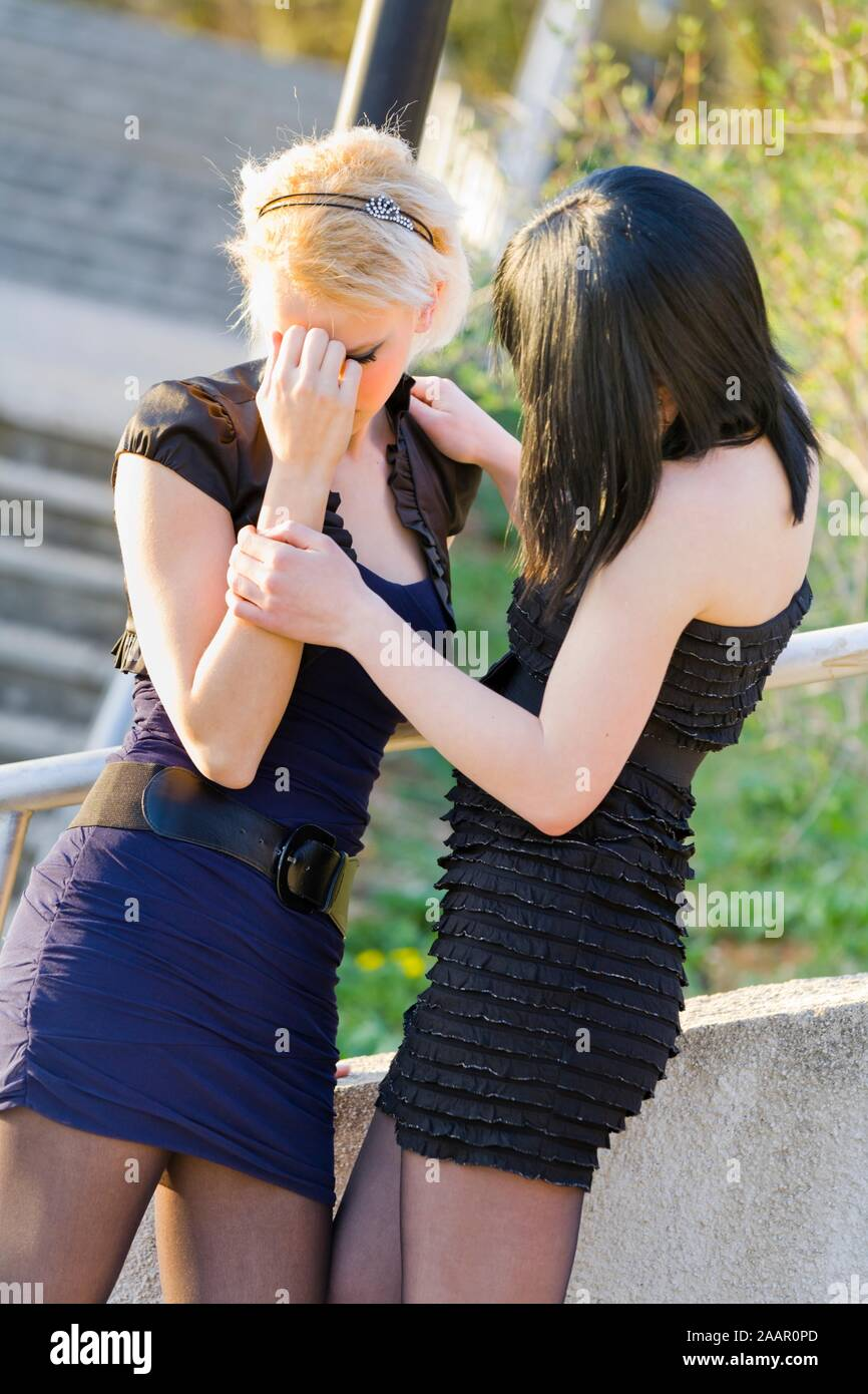 Pretty girlfriends compassion friendship short mini skirt clothing upset empathy girls teen crushed young-woman stressed polite teenage wearing Stock Photo