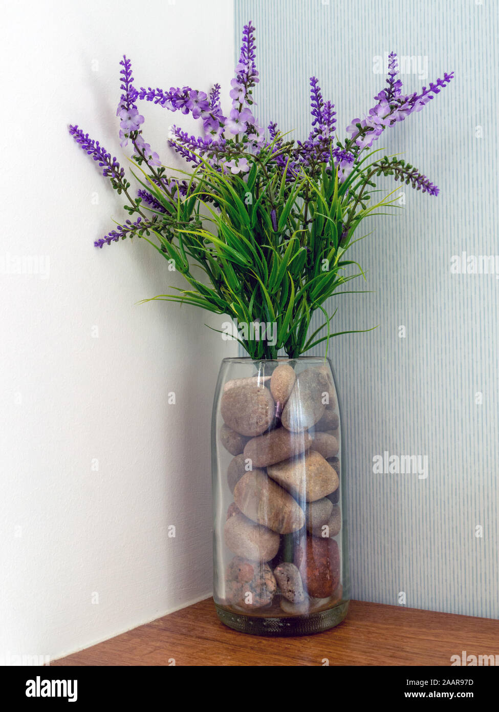 Attractive And Simple Artificial Flower Arrangement Of Purple Lavender Flowers And Pebbles In A Glass Vase Stock Photo Alamy