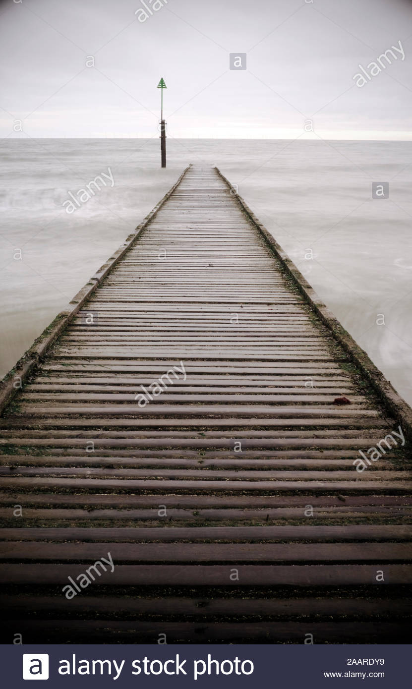 Narrow wooden walkway leading in to a grey sea. Stock Photo