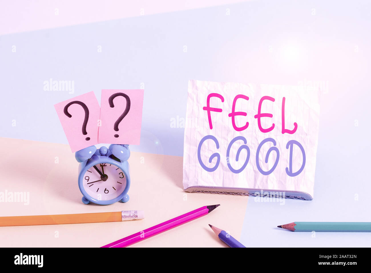 Writing note showing Feel Good. Business concept for relating to or promoting an often specious sense of satisfaction Mini size alarm clock beside sta Stock Photo