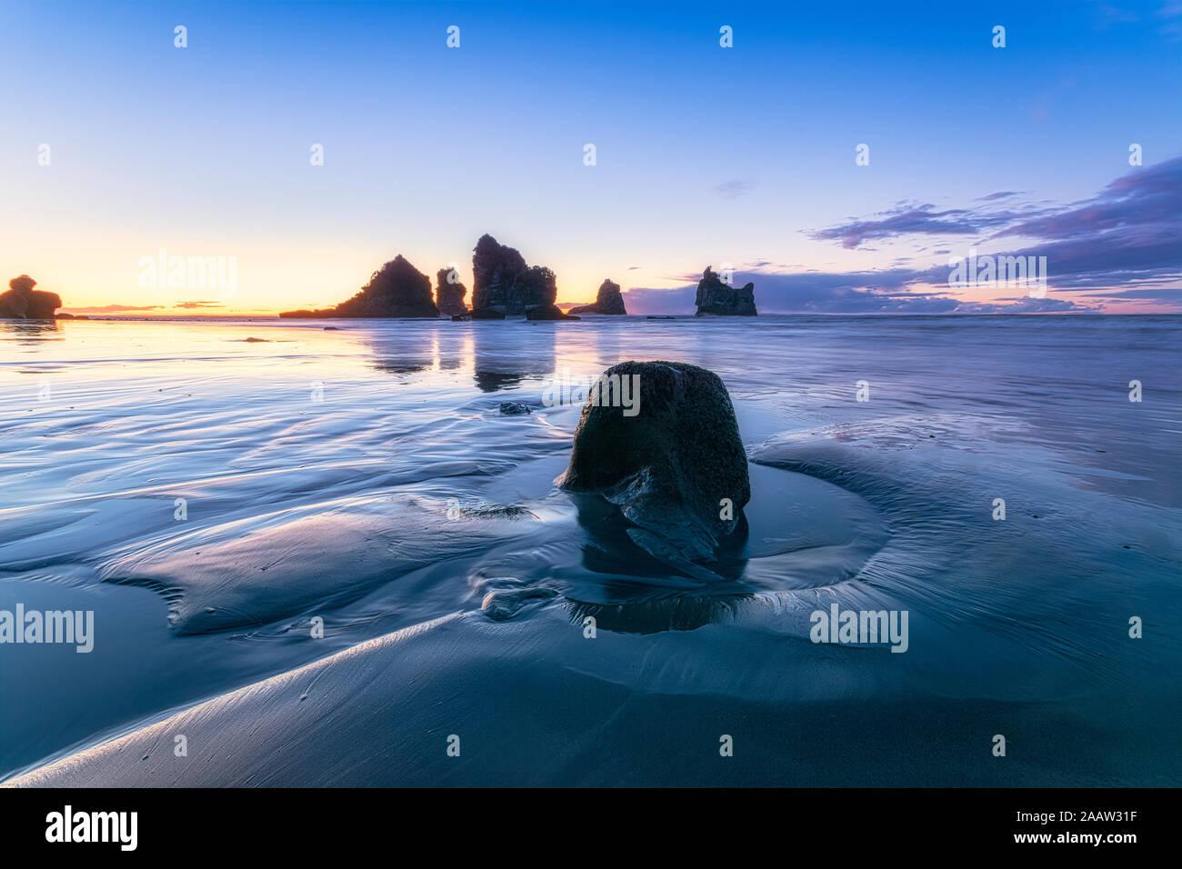 New Zealand, South Island, Silhouettes ofMotukiekieBeach sea stacks at sunset Stock Photo