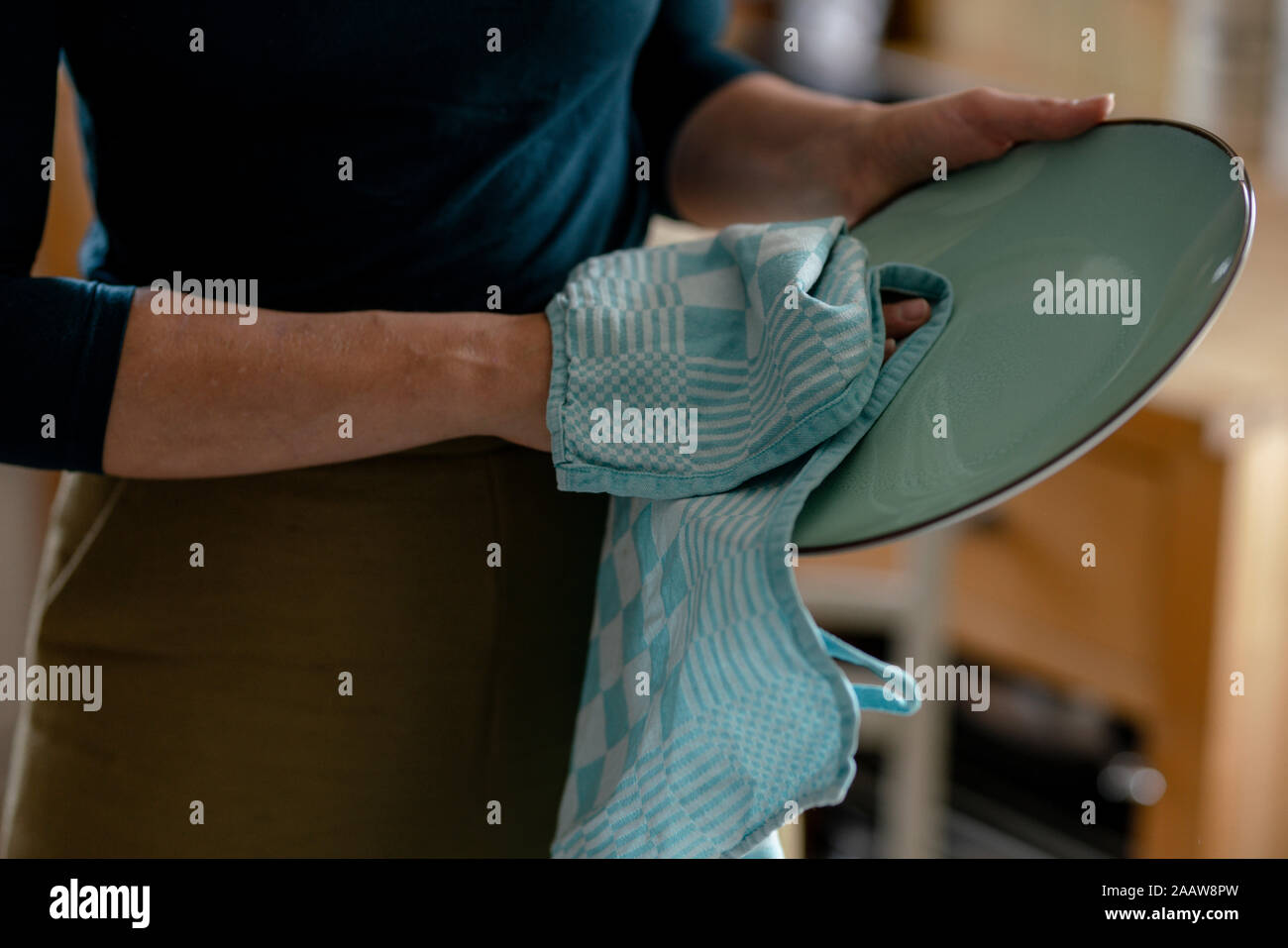 Woman drying plate with dish towel, close-up Stock Photo