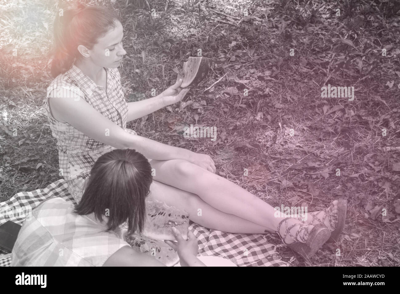 Two young women enjoying  conversation and eating watermelon on picnic outdoors Stock Photo