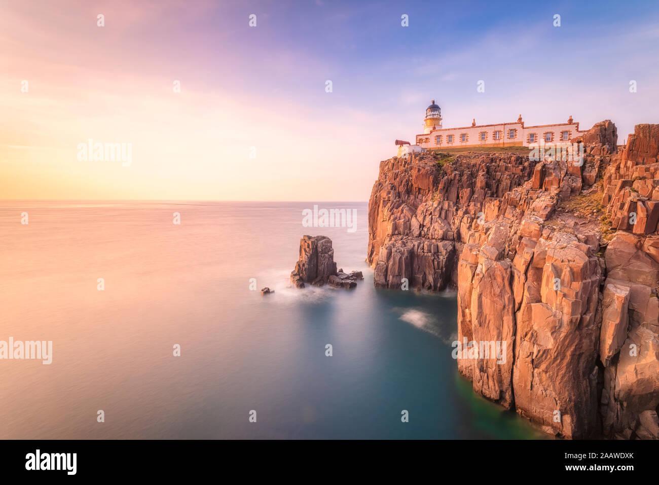 Neist Point Lighthouse by sea during sunset, Waterstein, Isle of Skye, Highlands, Scotland, UK Stock Photo