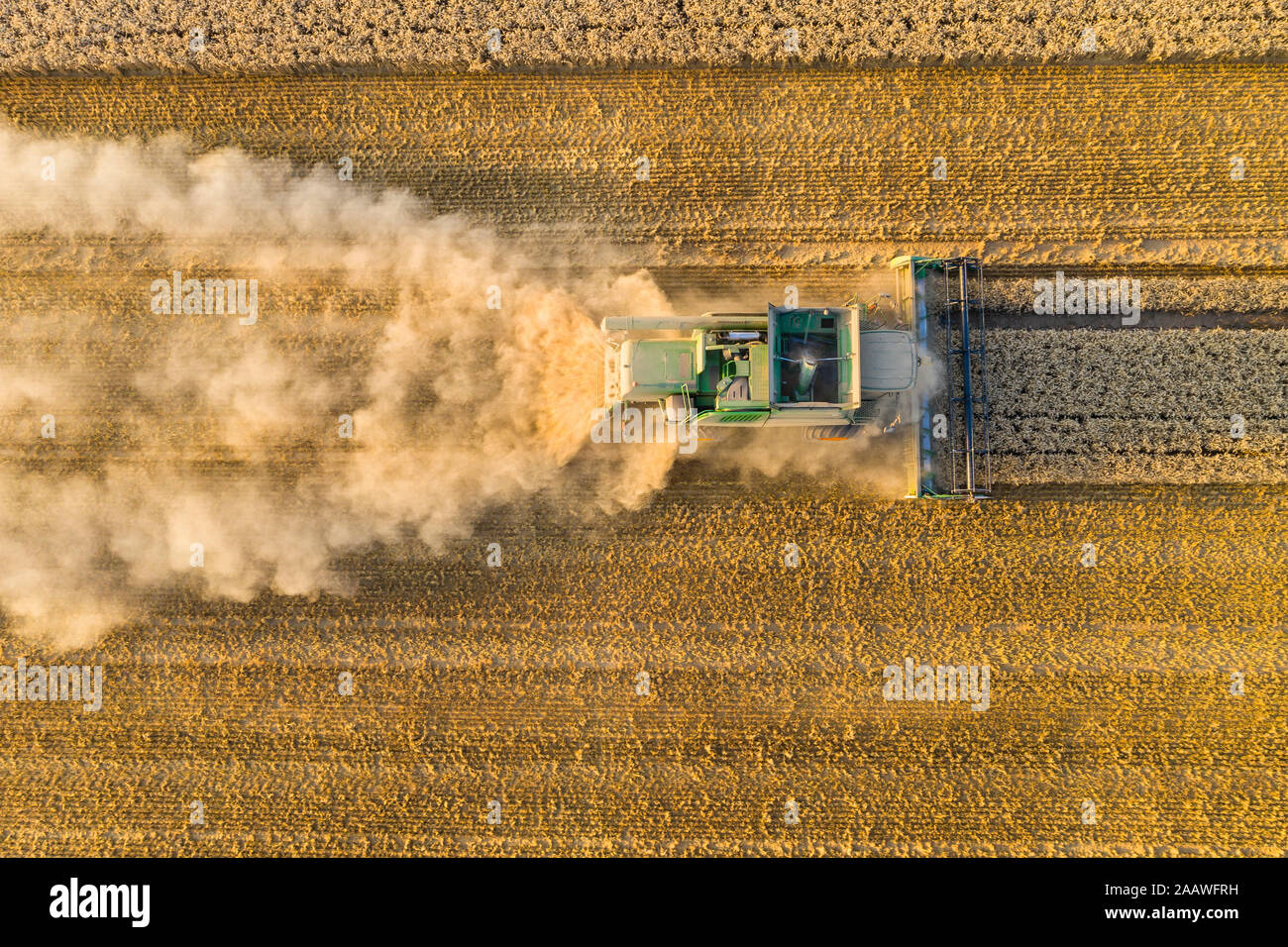Aerial view of combine harvester on agricultural field during sunset Stock Photo