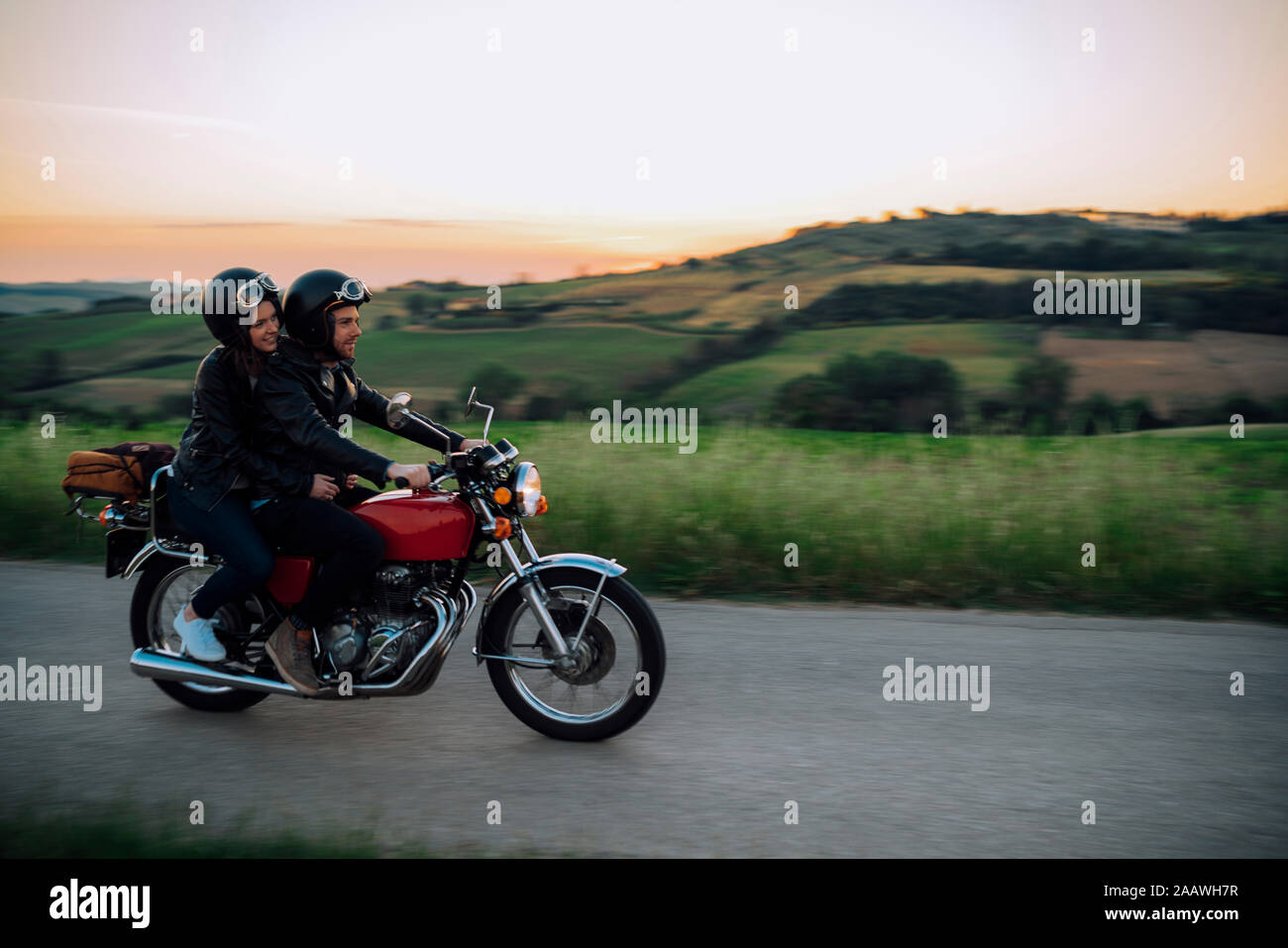 Young couple riding vintage motorbike on country road at sunset, Tuscany, Italy Stock Photo