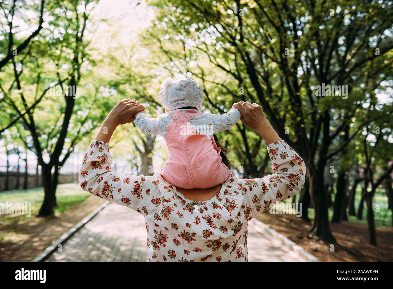 Mother walking in a park with baby girl on her shoulders Stock Photo