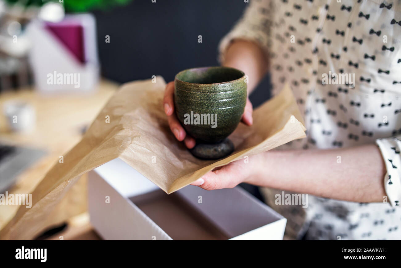Close-up of woman wrapping an earthenware mug Stock Photo
