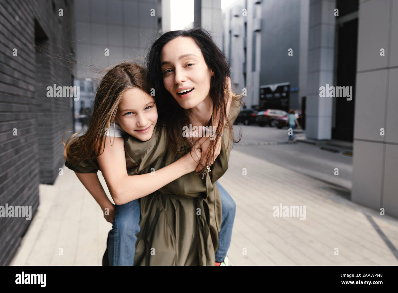 Portrait of mother giving her daughter a piggyback ride Stock Photo