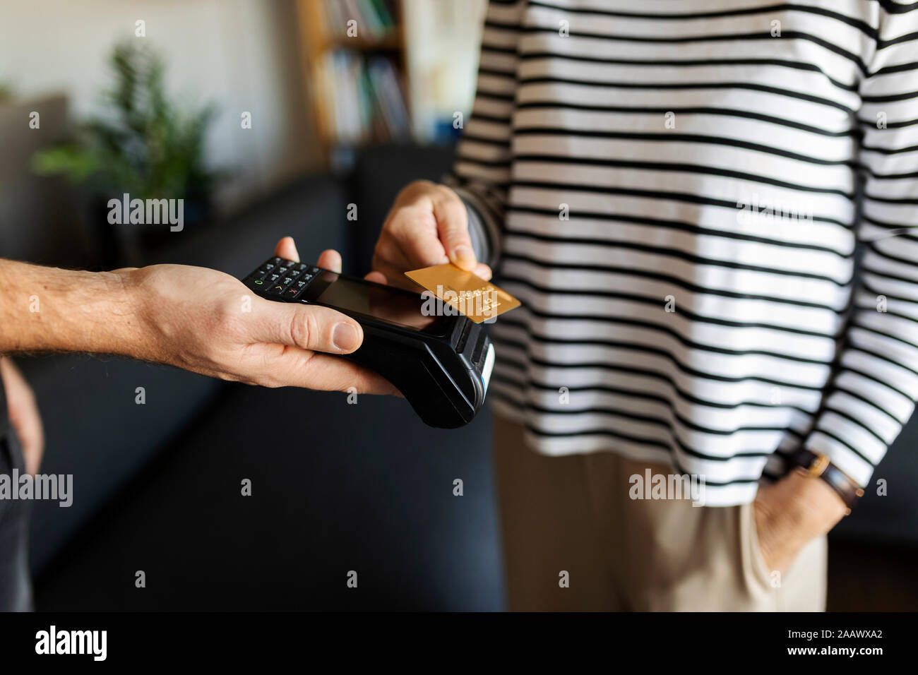 Close-up of woman paying with credit card at home Stock Photo