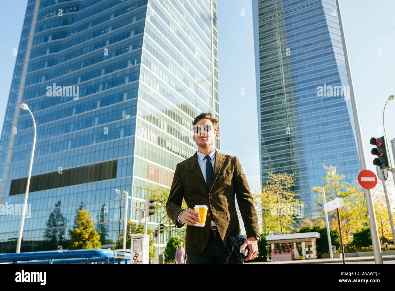 Confident businessman walking in urban business district, Madrid, Spain Stock Photo