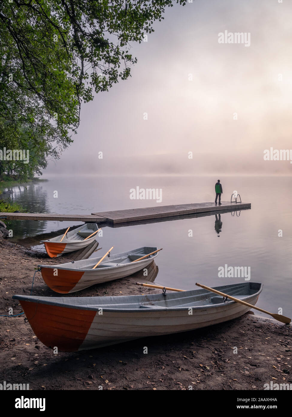 Tranquil beauty morning with row boat and pier at misty summer sunrise in idyllic beach Finland Stock Photo