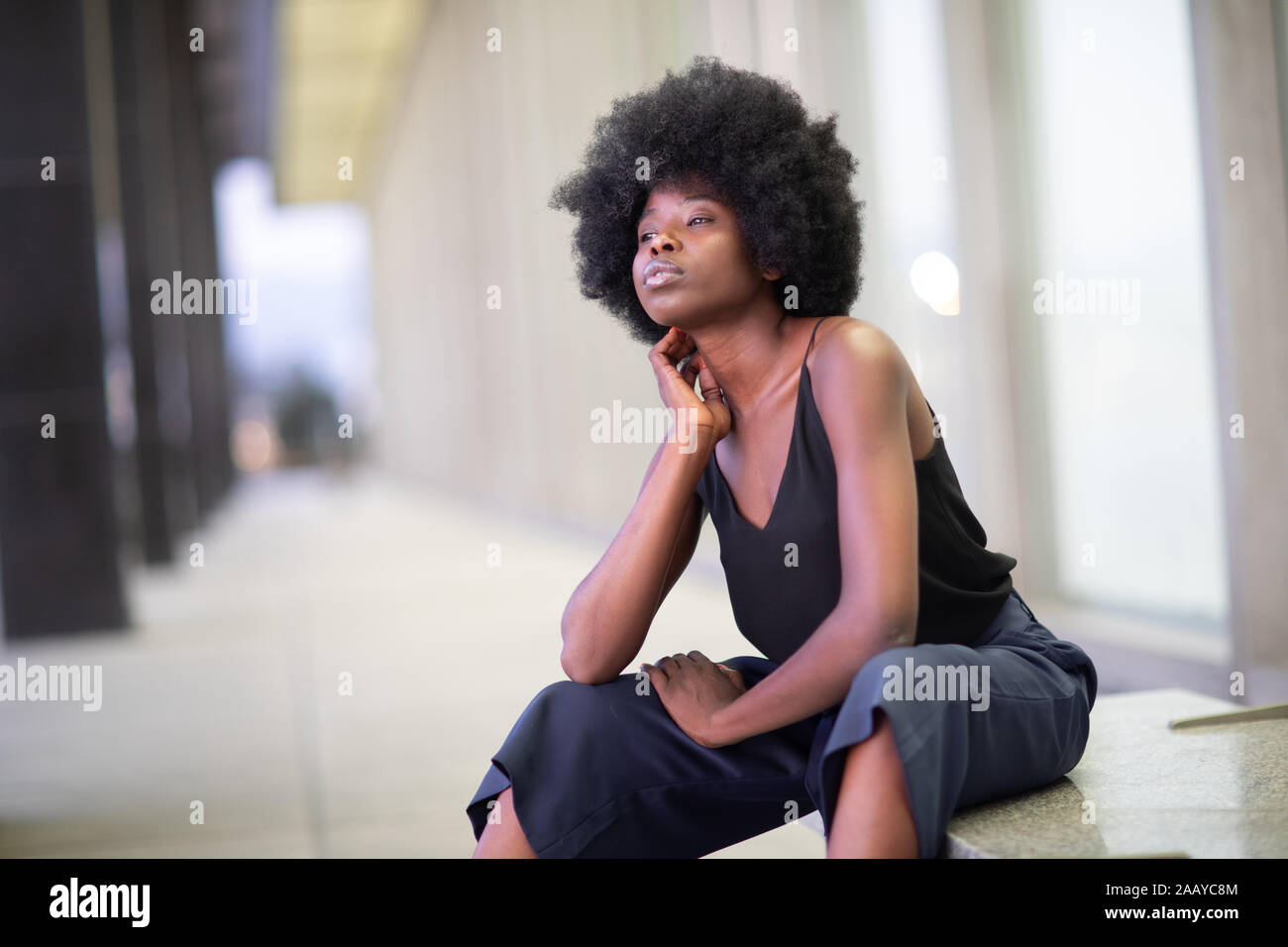 Pretty young African American woman on city streets, sitting on the bench Stock Photo