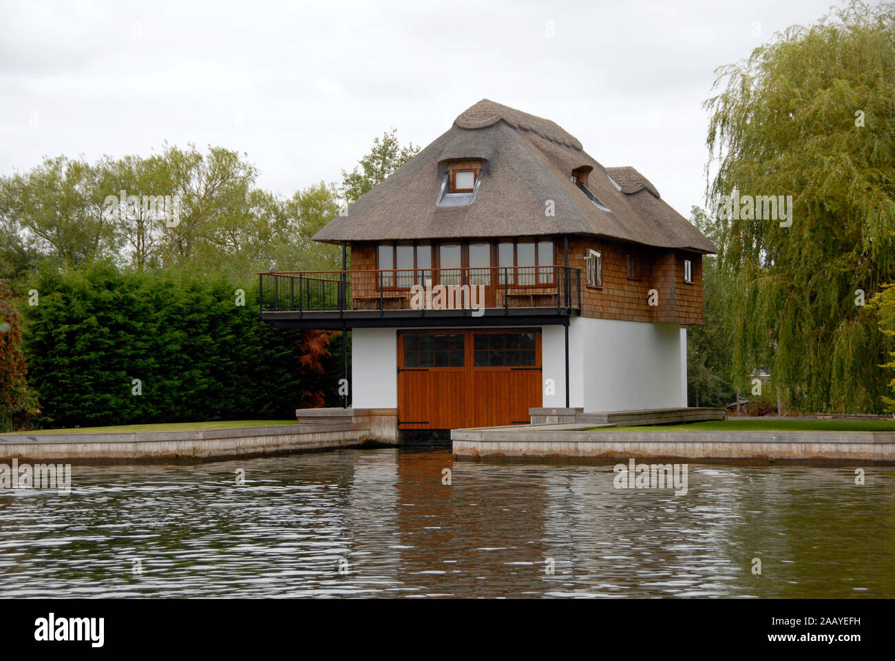 Attractive riverside thatched house built over boathouse, Norfolk Broads, England Stock Photo