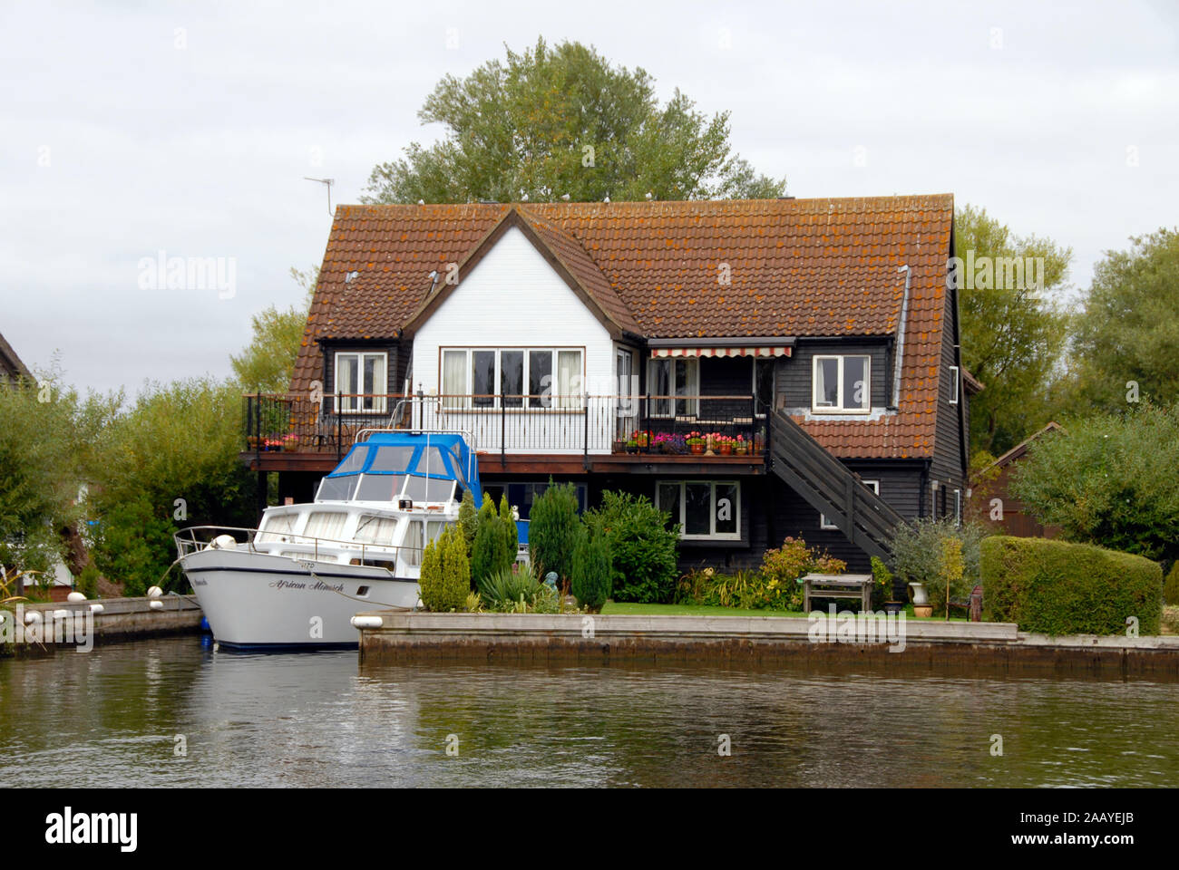 Attractive two-storey riverside house with motor cruiser moored in front, Norfolk Broads, England Stock Photo