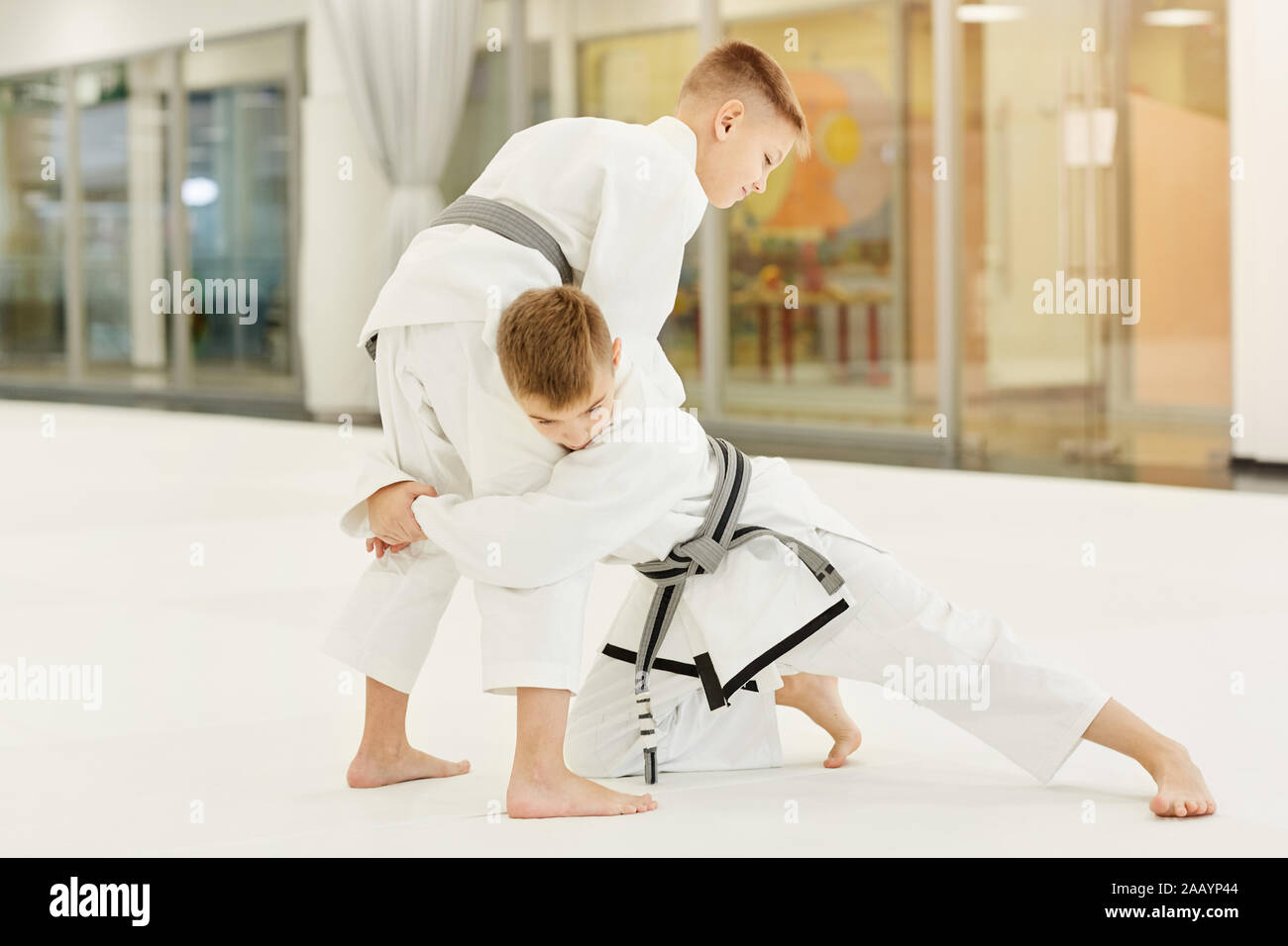 Two boys in white kimono fighting with each other during training in karate in gym Stock Photo